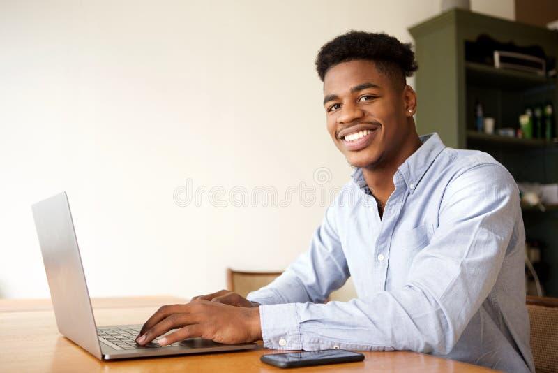 Powabny młody amerykanin afrykańskiego pochodzenia mężczyzna pracuje z laptopem przy biurem obraz royalty free
