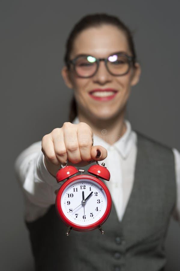 Powabny m?ody bizneswomanu lub urz?dnika mienia czerwieni zegar w r?kach obrazy royalty free