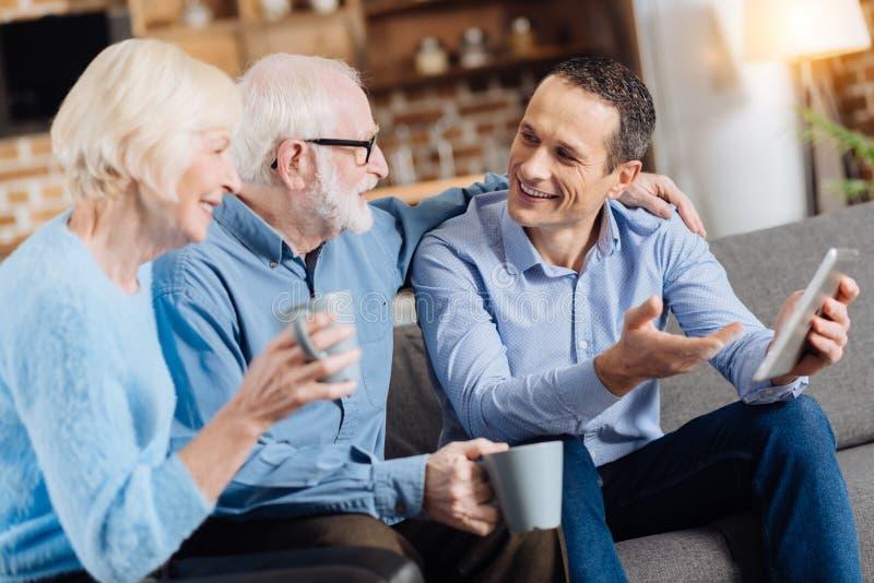 Powabny młody człowiek ma dyskusję z jego starszymi rodzicami obrazy royalty free