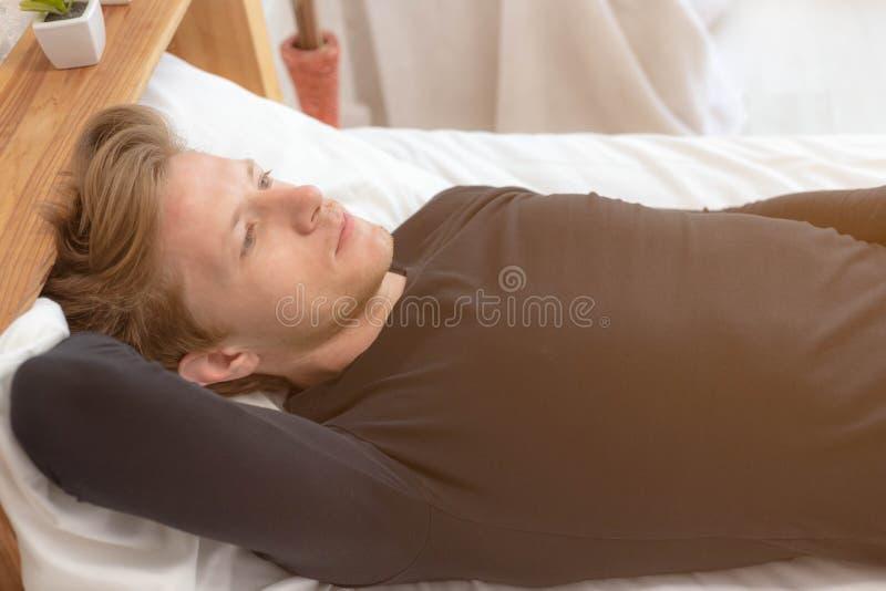 _powabny przystojny młody facet główkowanie coś o jego przyszłościowy życie na łóżko przy sypialnia Atrakcyjny przystojny mężczyz fotografia stock