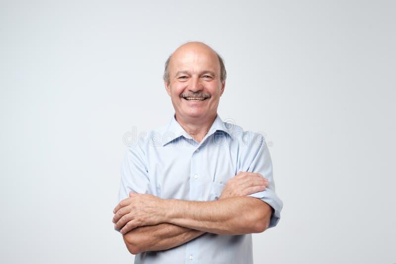 Powabny przystojny starszy mężczyzna utrzymuje ręki krzyżować w przypadkowej błękitnej koszula i ono uśmiecha się fotografia royalty free