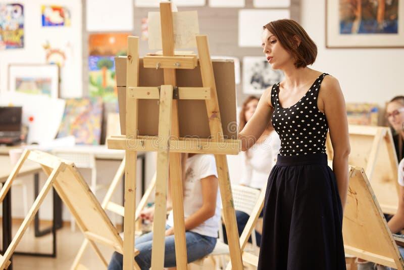 Powabny rysunkowy nauczyciel w pi?knej sukni pokazuje rysunkow? technik? przy sztalug? w sztuki studiu fotografia royalty free