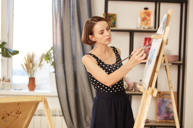 Powabny rysunkowy nauczyciel w pi?knej sukni pokazuje rysunkow? technik? przy sztalug? w sztuki studiu zdjęcia stock