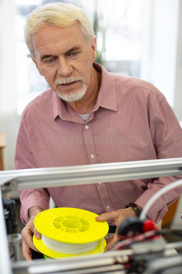 Powabny starszego mężczyzna mienia drucik dla 3D drukarki obraz royalty free