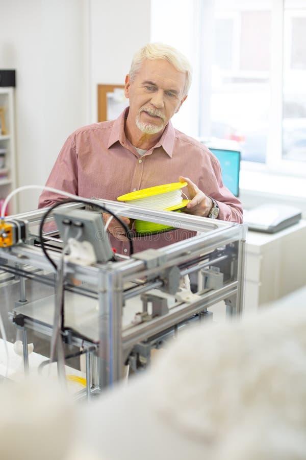 Powabny starszy mężczyzna niesie out 3D drukarki utrzymanie fotografia stock