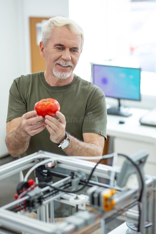 Powabny starszy mężczyzna pokazuje drukowanego pomidoru koledzy obraz royalty free