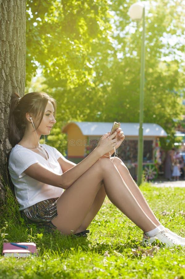 Powabny Studencki dziewczyny obsiadanie na Zielonej trawie zdjęcie stock