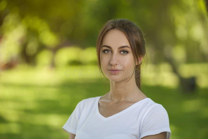 Powabny Studencki dziewczyny obsiadanie na Zielonej trawie zdjęcia royalty free