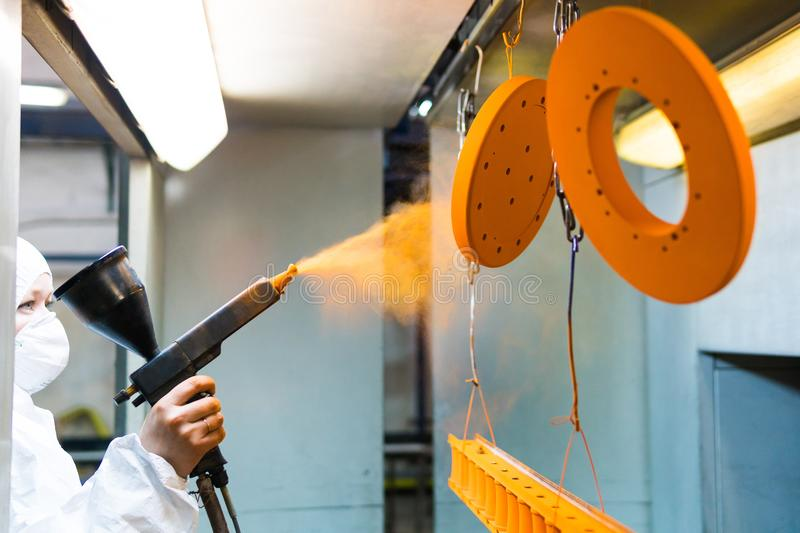 Powder coating of metal parts. A woman in a protective suit sprays powder paint from a gun on metal products. Powder coating of metal parts. A man in a royalty free stock photography