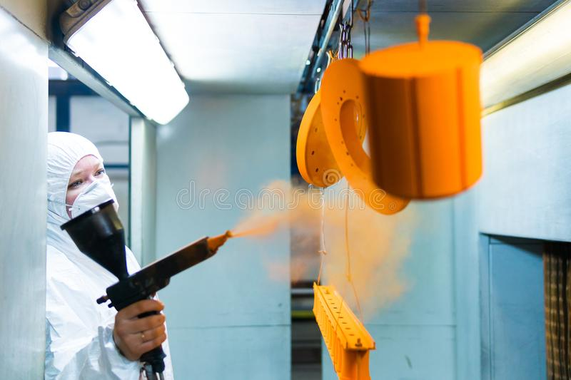 Powder coating of metal parts. A woman in a protective suit sprays powder paint from a gun on metal products stock photos