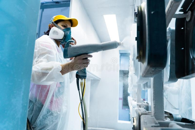 Powder coating of metal parts. A woman in a protective suit sprays white powder paint from a gun on metal products royalty free stock images