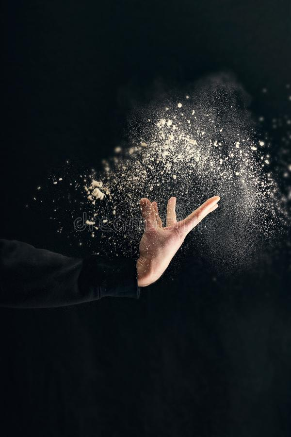 Powder explosion with hand isolated on black background stock photography