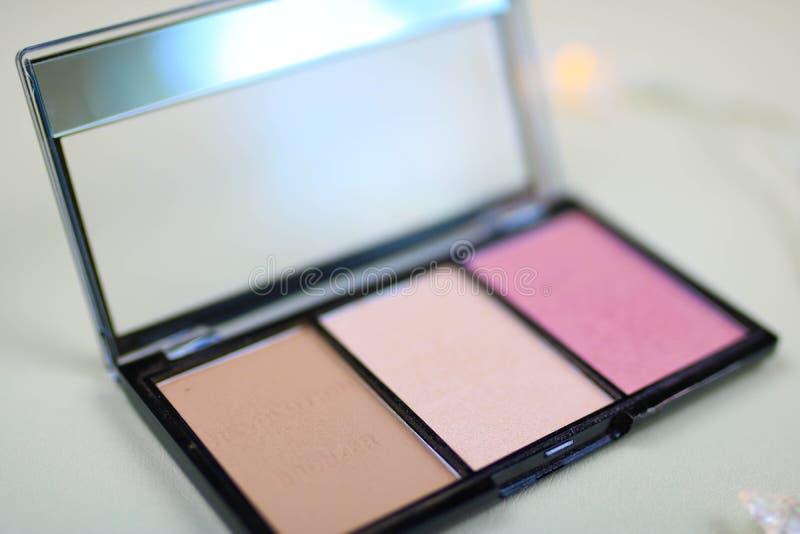 Powder pallet, blush, bronzer. Open powder box with beige powder and pink blush, professional brush. Compact pallet of bronzer and blush stock image