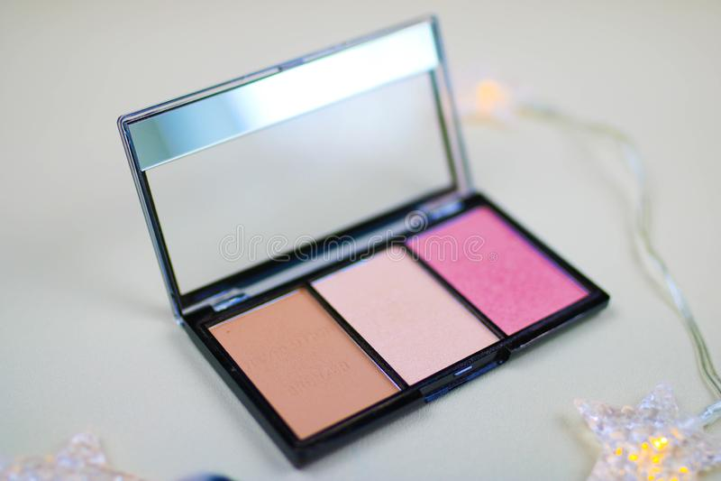 Powder pallet, blush, bronzer. Open powder box with beige powder and pink blush, professional brush. Compact pallet of bronzer and blush stock photo