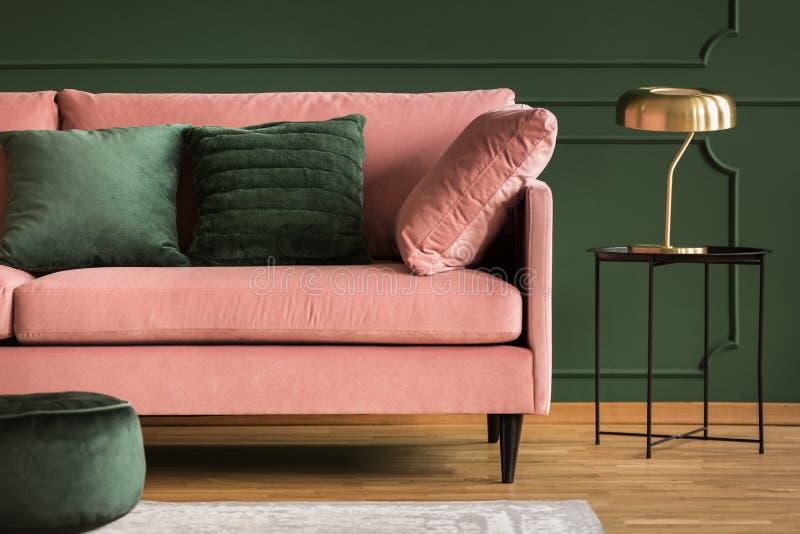 Powder pink sofa and golden lamp in a dark green living room interior. Real photo. Powder pink sofa and golden lamp in a dark green living room interior. photo stock photos