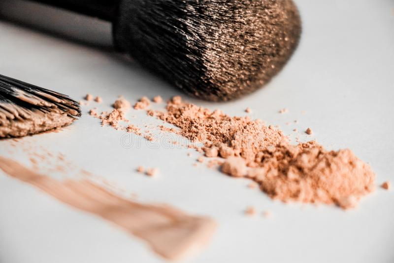 Powder slide, a touch of foundation and two black makeup brushes royalty free stock photo