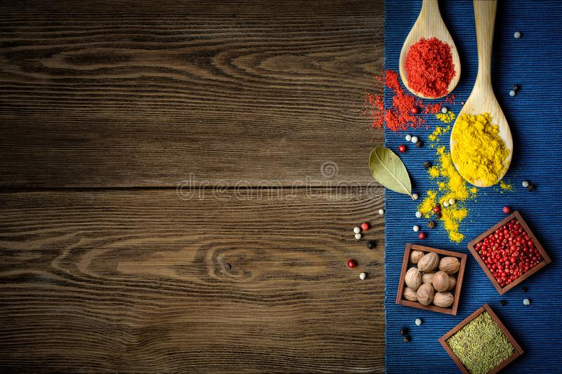 Powder spices on spoons and box on wooden background. Colorful spices on spoons and in wooden box on dark wooden table background with blue cloth border, top royalty free stock photo