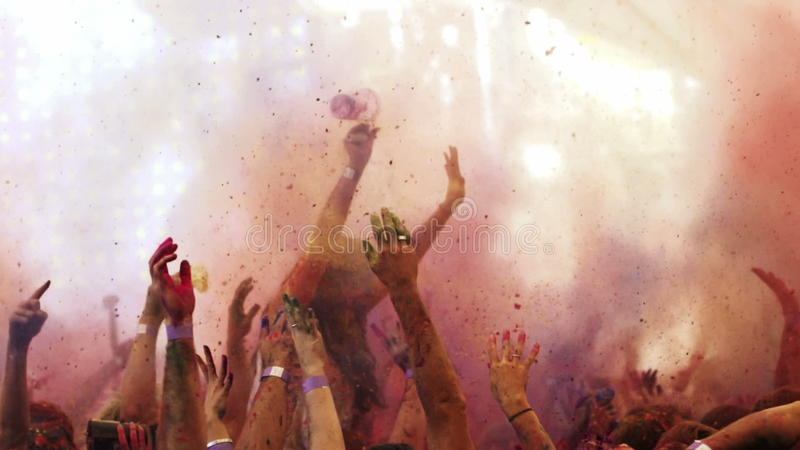 Powder is thrown at holi colour festival in slow motion. A colourful shot of music fans throwing coloured powder into the air at holi colour festival in slow stock video footage