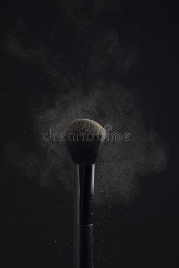 Powderbrush with cloud of face powder on black background.  royalty free stock photos