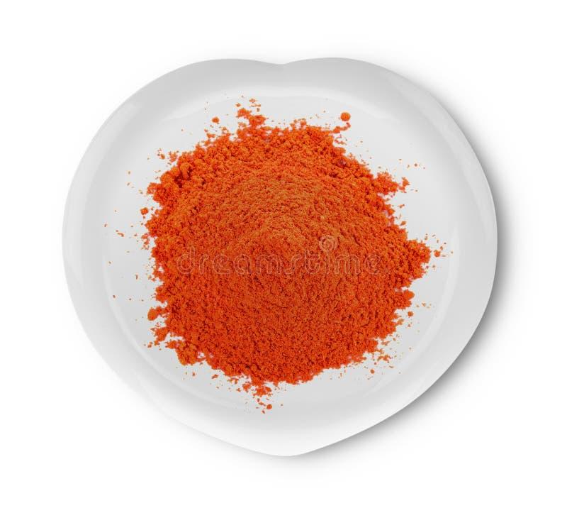 Powdered высушил красный пеец в современной керамической плите на белом backg стоковые фото
