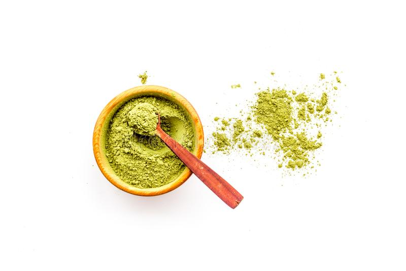 Powdered matcha green tea in bowl and scattered on white background top view copy space royalty free stock images