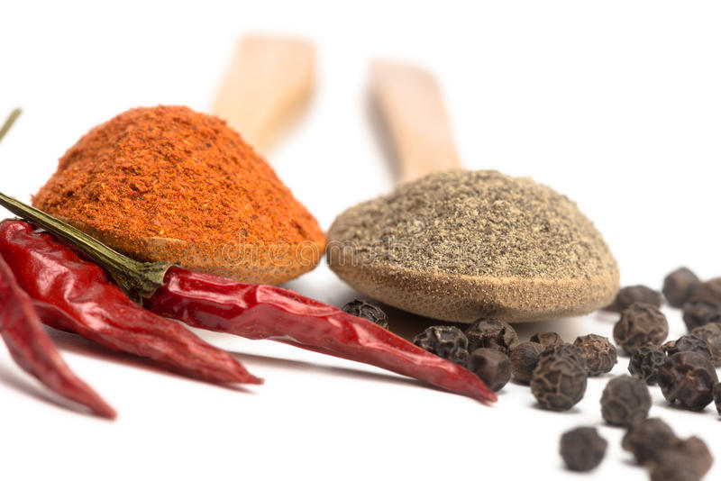Powdered pepper red and black. Ground red and black pepper in a spoon isolated royalty free stock photography