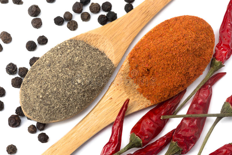 Powdered pepper red and black. Ground red and black pepper in a spoon isolated royalty free stock images