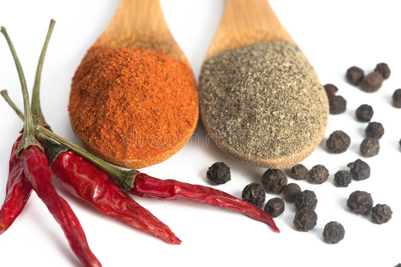 Powdered pepper red and black. Ground red and black pepper in a spoon isolated royalty free stock photo