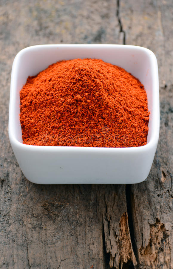 Powdered red pepper. In a white bowl royalty free stock photography