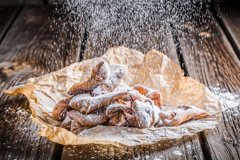 Powdered sugar falling on angel wings. On old wooden table stock photo