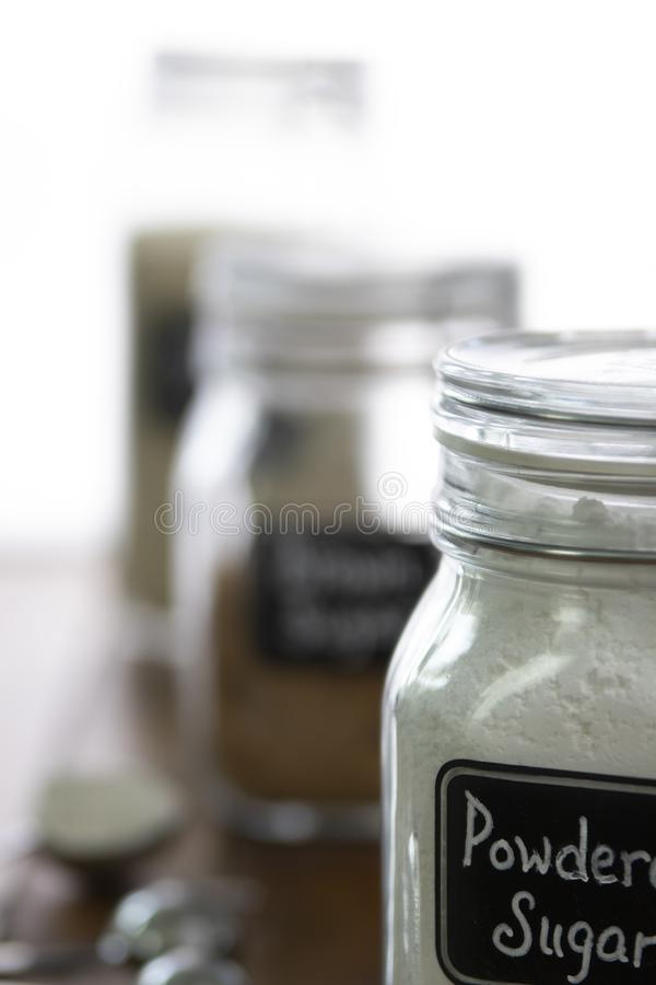 Powdered sugar in a jar with other baking ingredients on out of focus background stock photo