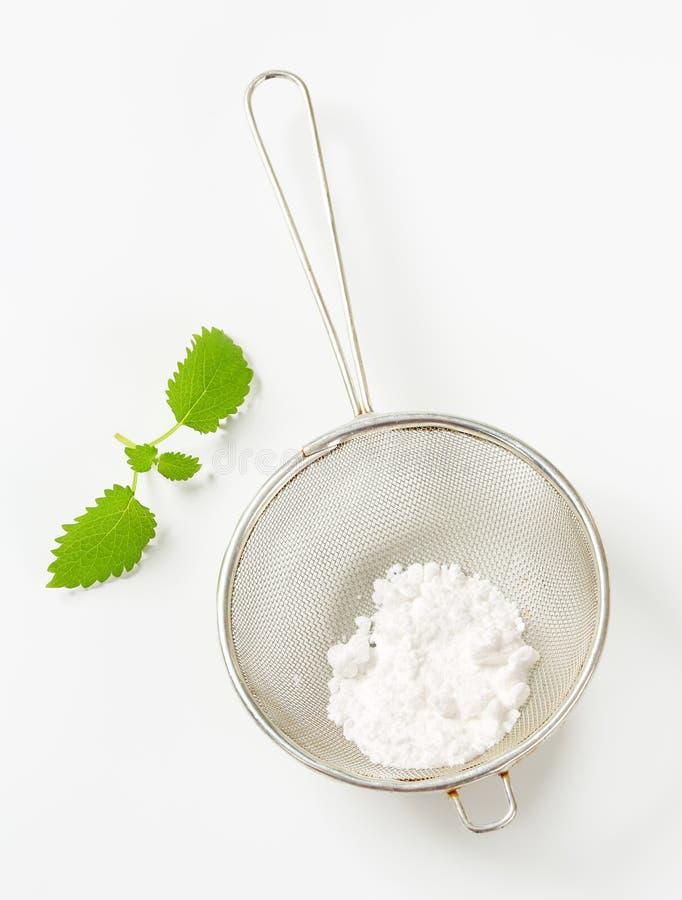 Powdered sugar in a sieve. Icing sugar in a sieve stock photo