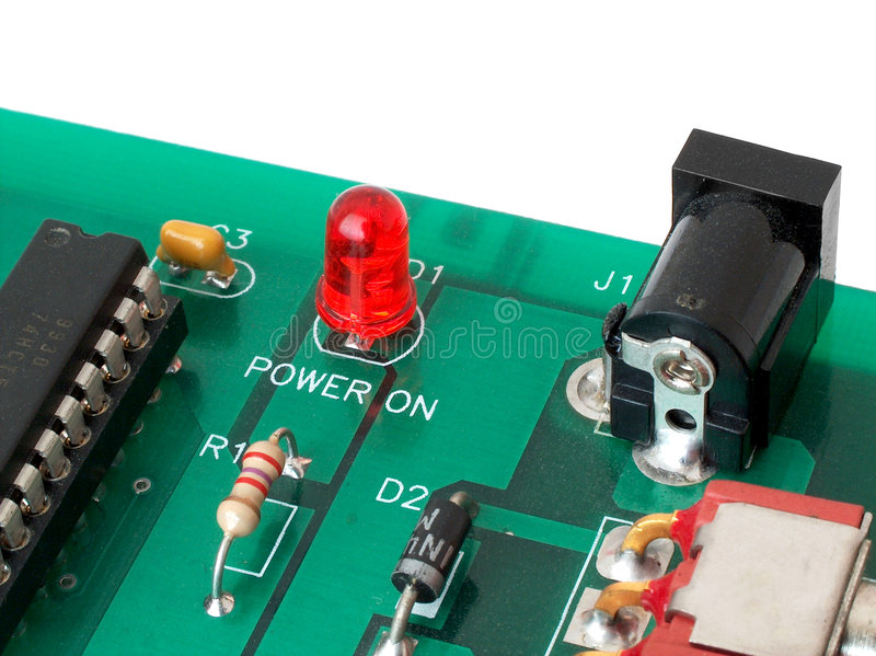 Power On. Dusty printed circuit board with some components soldered in. From the bottom left: integrated circuit (chip) on a socket; resistor; diode; power royalty free stock image