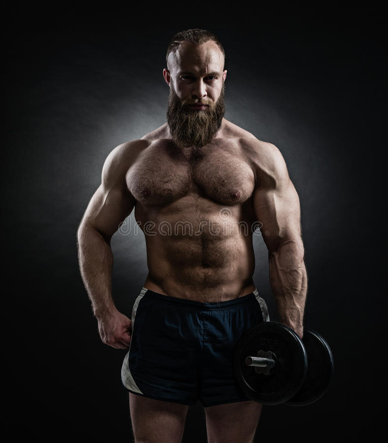 Power athletic bearded man in training pumping up muscles with d stock photos