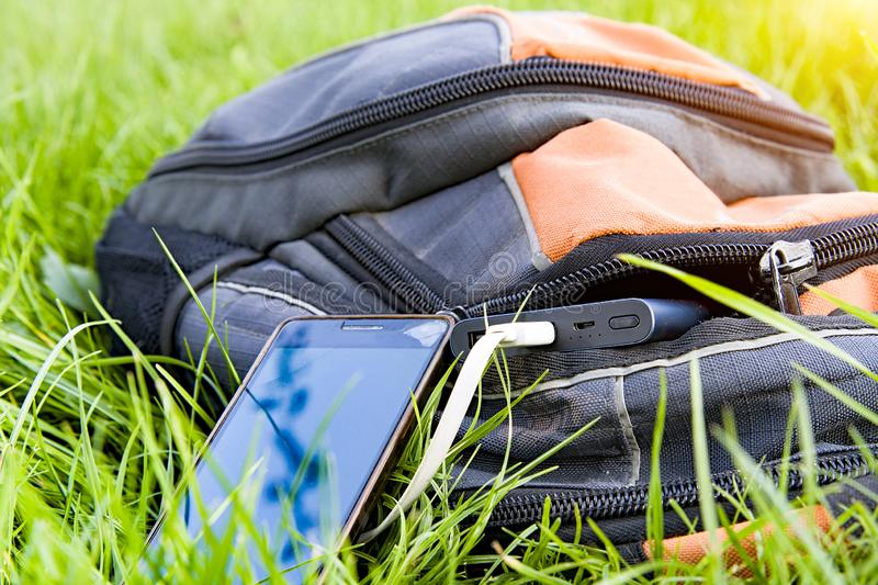 Power bank charges. A smartphone on the grass royalty free stock photos