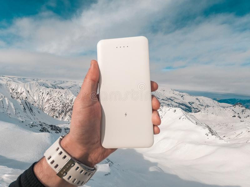 Power bank in hands. Tourist charges a devices in nature, against the backdrop of a winter mountains landscape. Power bank in hands. Charges a devices in nature royalty free stock images