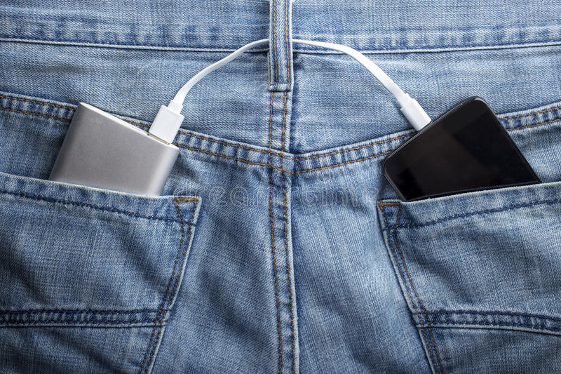 power bank lies in a back pocket of jeans the mobile phone charges stock image