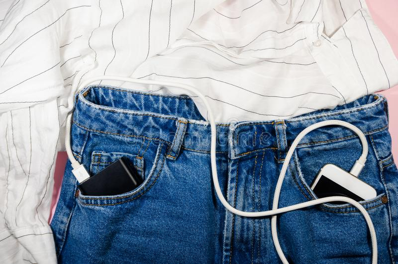Power bank and a phone  in jeans royalty free stock photo