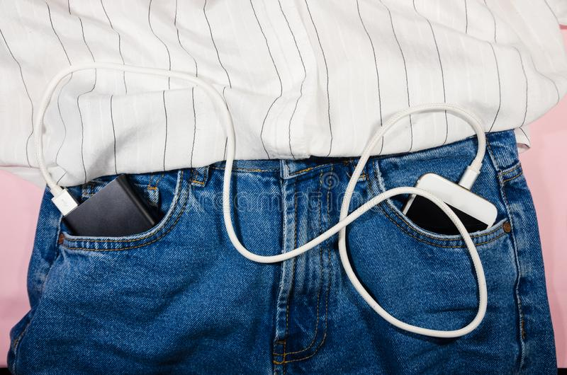 Power bank and a phone  in jeans stock photo
