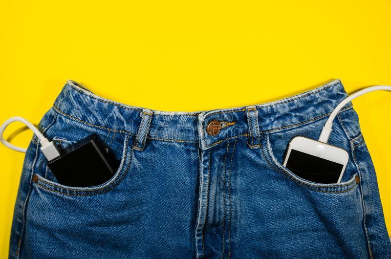 Power bank and a phone  in jeans stock image