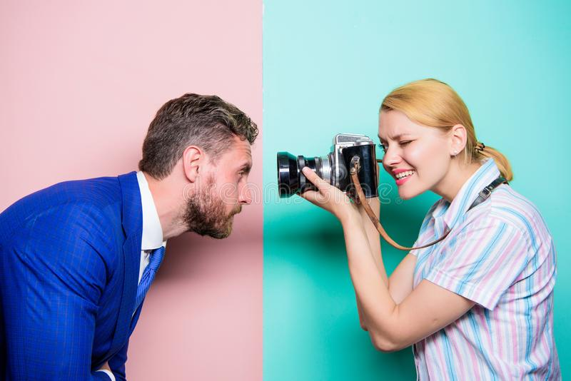 The power behind the picture. Businessman posing in front of female photographer. Pretty woman using professional camera royalty free stock photography