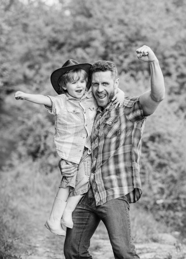 Power being father. Child having fun cowboy dad. Rustic family. Growing cute cowboy. Small helper in garden. Little boy. And father in nature background. Spirit royalty free stock photography