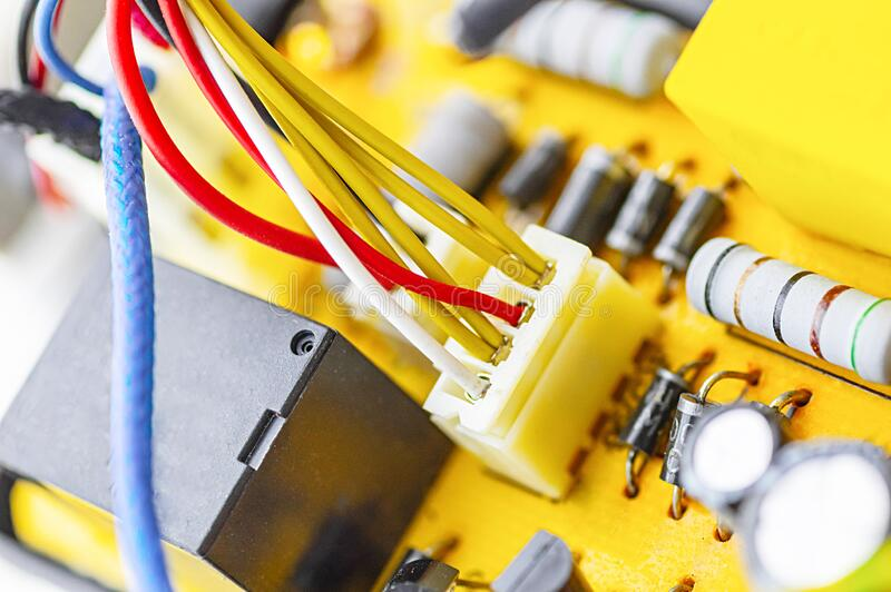 Power board for an electrical appliance. Multicolored electrical cables, condenser. Selective focus. Power board for an electrical appliance. Multicolored stock photo