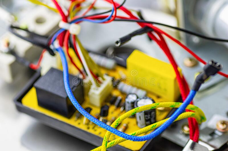 Power board for an electrical appliance. Multicolored electrical cables, condenser. Selective focus. Power board for an electrical appliance. Multicolored stock images