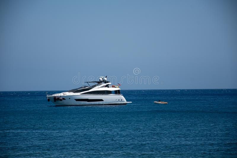 Power boat and Dinghy. Perissa, Greece - July 11 2019:   A power boat anchored with a dinghy in tow in the deep blue waters of the Aegean Sea off Perissa Beach royalty free stock photos