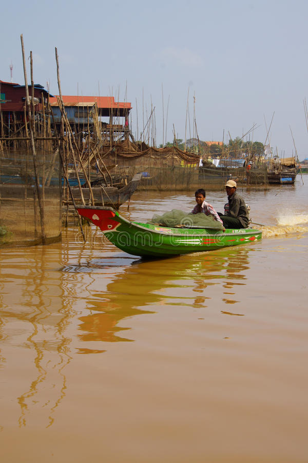 Power boat travels waterway. KOMPONG KLEANG, CAMBODIA - FEB 12, 2015 - Power boat travels along the waterway of Kompong Kleang floating fishing village, Cambodia stock image