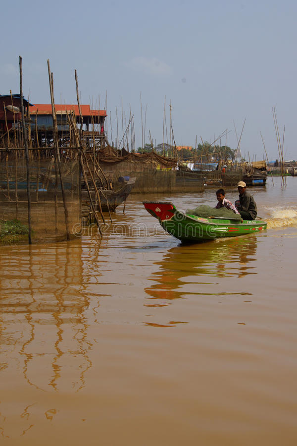 Power boat travels waterway. KOMPONG KLEANG, CAMBODIA - FEB 12, 2015 - Power boat travels along the waterway of Kompong Kleang floating fishing village, Cambodia royalty free stock photo