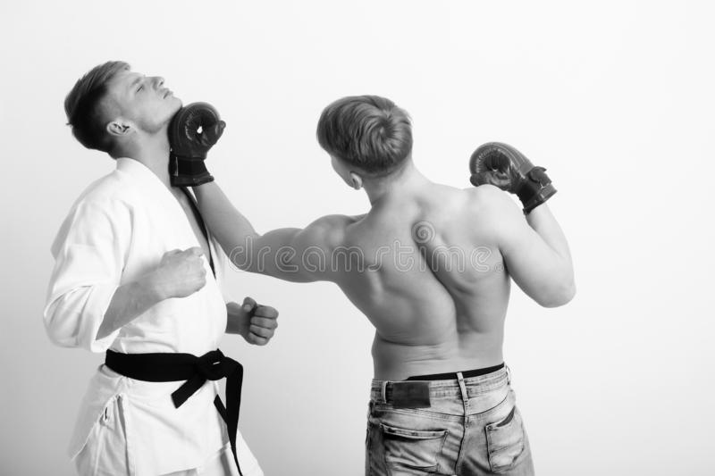 Boxer punching young karate athlete royalty free stock photo
