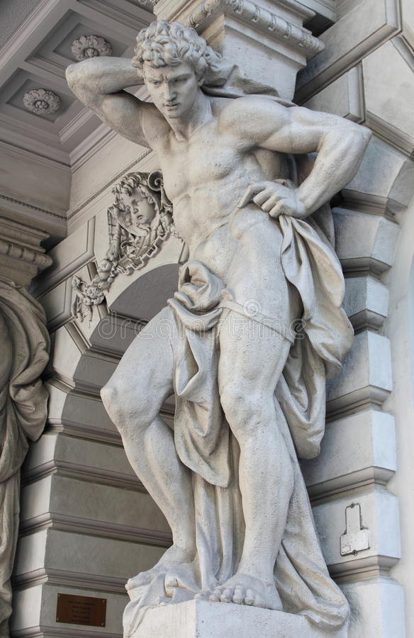 Power. Brawny statue supporting a column on a renaissance palace. Metaphor of power stock photo