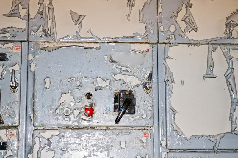 The power button and knob toggle switch to control industrial equipment at the factory on the background of a wall with shabby stock photos
